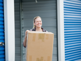 Person holding box in front of self storage unit