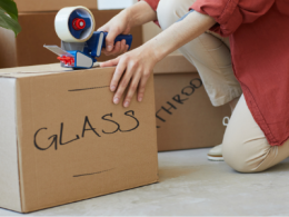 Person taping moving box labelled glass