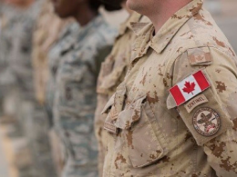 Man in military uniform with Canadian Flag